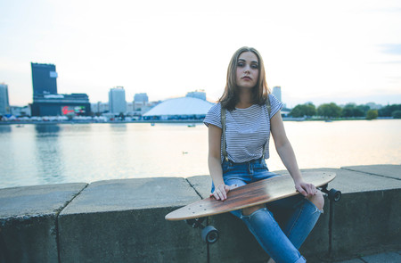 Portrait of young stylish hipster girl with longboard skateboard in a urban background