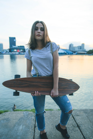 Portrait of young teen hipster girl with longboard skateboard on the street Imagens