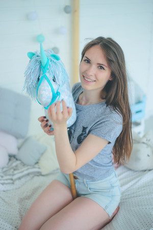 Portrait of cute smiling teen girl sitting on the bed with plush unicorn Imagens