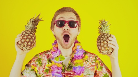 Happy lucky young man standing on yellow background with hawaiian shirt and two pineapples