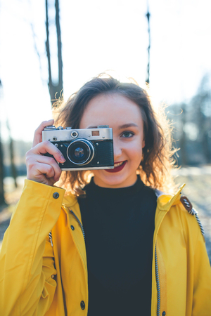 Teen hipster girl photographer taking images with retro vintage camera at sunset