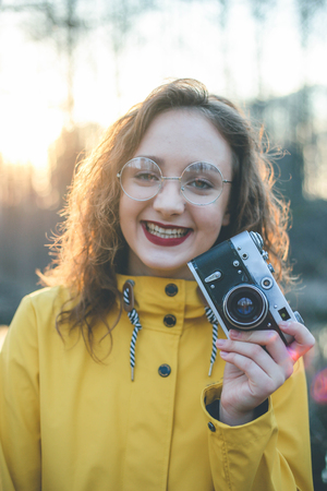 Portrait of smiling teen girl photographer in glasses with retro vintage camera at sunset Imagens