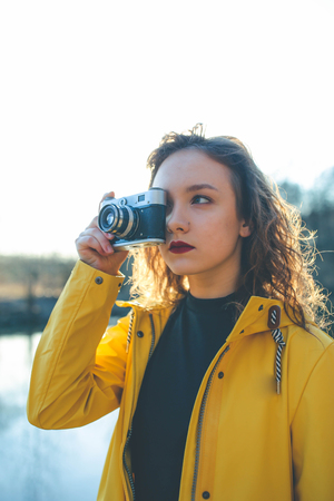 Portrait of teen hipster girl in yellow jacket photographer in yellow jacket with retro vintage camera at sunset