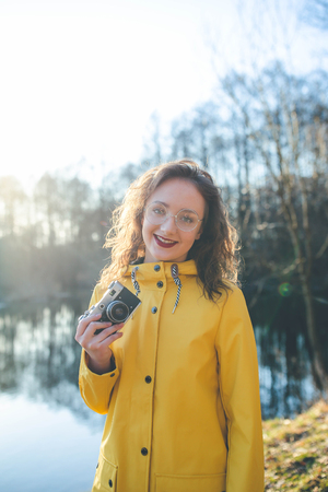 Vintage young hipster girl photographer in yellow jacket holding retro camera Imagens