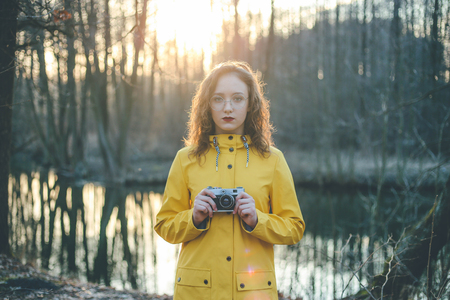 Portrait of teen hipster girl photographer in glasses with retro vintage camera at sunset Imagens