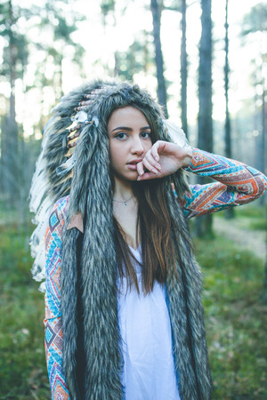 Portrait of young dramatic girl with Indian feather hat roach in forest