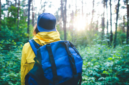 Back view of traveler hipster girl with backpack walking in the forest. Tourism, traveling, hiking and healthy lifestyle concept.