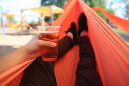 Man with beer relaxing in the hammock on a summer day