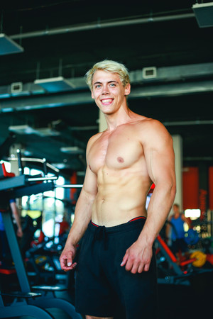 Portrait Of Smiling Blonde Muscular Man Standing In Gym Imagens