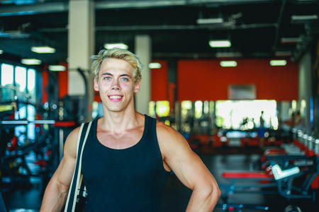 Portrait of young smiling man athlete with bag standing in gym