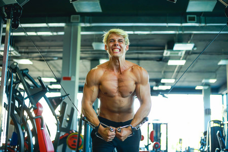 Portrait of young man grimacing while lifting weights at gym