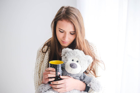 Portrait of the beautiful young woman with teddy bear plush and cup of coffee in bedroom Imagens