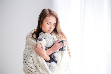Young beautiful woman holding teddy bear plush and cup of coffee in bedroom