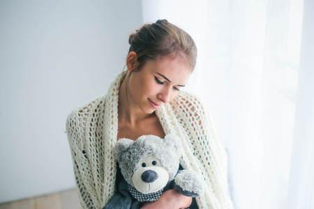Young beautiful woman holding teddy bear plush for Valentines Day