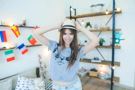 Lifestyle portrait of young hipster student girl with hat at home