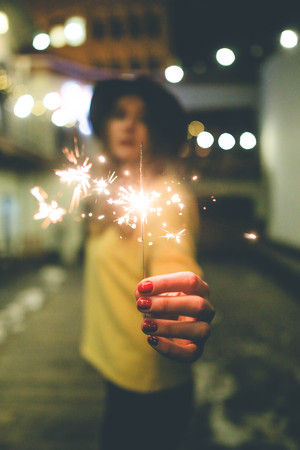 A young girls hand holding lighter burning Christmas sparkler Imagens