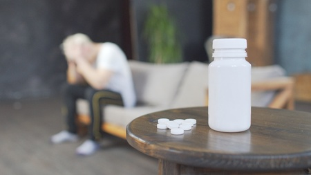 Sad young man with headache sitting on sofa at home with a pills on the table