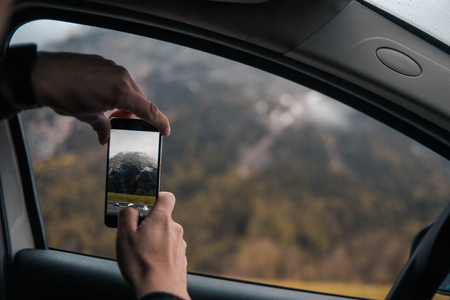 Man traveler taking photo of mountain landscape with a smartphone in his car. Travel by car concept. Copyspace Imagens