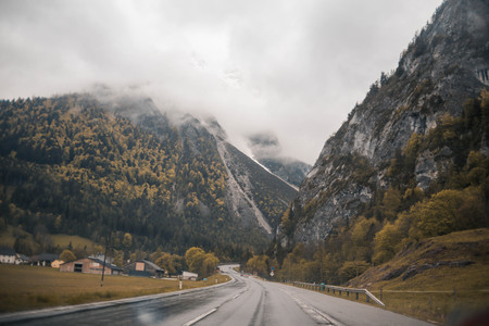 Asphalt mountain road in austrian alps in rainy day