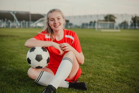 Portrait of smiling girl football player with soccer ball sitting on the grass, copy space