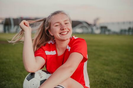 Portrait of smiling girl football player with soccer ball sitting on the grass Imagens