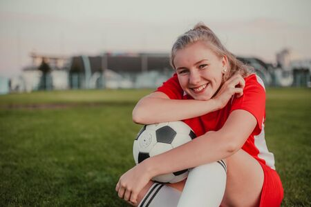 Portrait of cute girl soccer player with ball sitting on the grass, copy space Imagens
