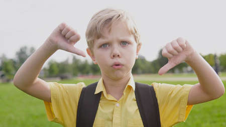 Emotional portrait of blond unhappy boy giving thumbs down hand