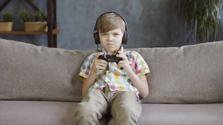 Child boy playing online video game with joystick and headphones Archivio Fotografico