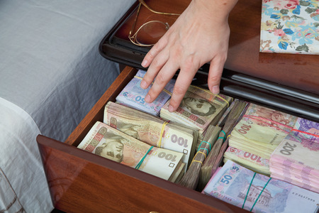 miser: Hand reaches for the money in bedside table filled with Ukrainian cash