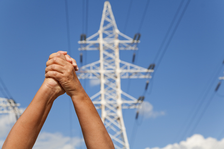assent: Hands crossed in assent against the background of power transmission lines and blue sky Stock Photo
