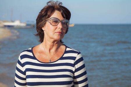 away: Pretty elderly woman in sunglasses on vacation at the seaside