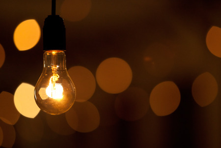 Burning bulb shines weakly on the background blurred yellow lights