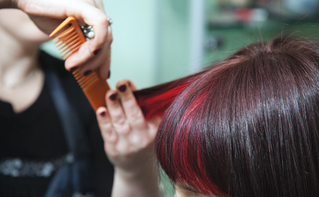 Hands of the hairdresser in motion during womens hairstyles with red hair strands Zdjęcie Seryjne