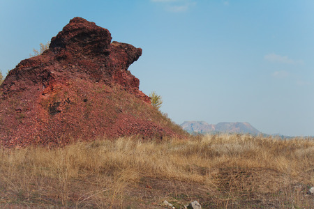 slag: Unusual shape slag heap in meadow with dry grass on background of blue sky and other waste dumps