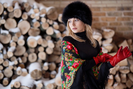 Russian beauty in a fur hat and traditional scarf