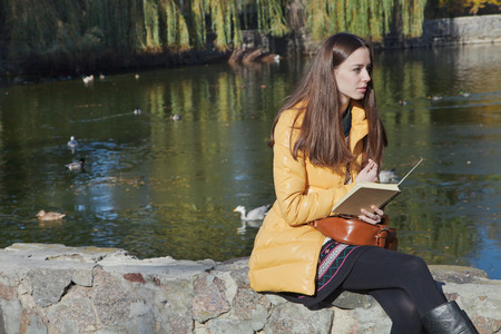 parapet wall: Beautiful thoughtful girl-student sits on parapet near the city pond in sunny autumn day