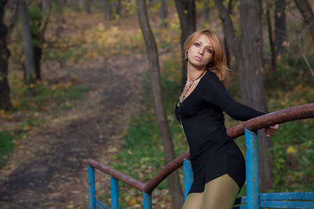 Beautiful blonde woman in a short black dress keeps for the railing of the bridge in autumn park