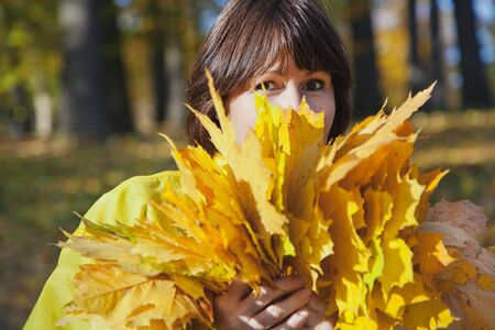 armful: Elderly attractive woman hiding her face behind armful yellow autumn leaves in forest on sunny afternoon Stock Photo