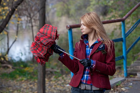 short gloves: Beautiful blonde in red gloves and short jacket opens checkered umbrella Stock Photo