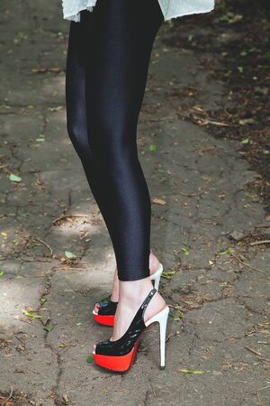 shapely legs: Shapely female legs in high heels dressed in black leggings on a forest path