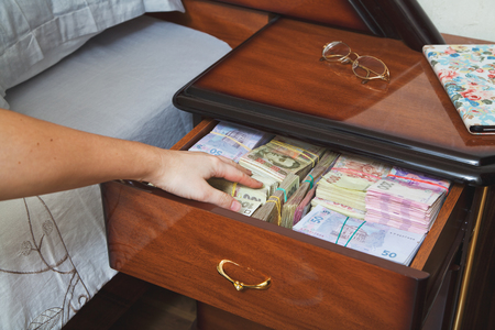 stingy: Hand reaches for the money in bedside table filled with Ukrainian cash