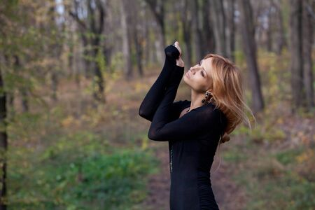 slinky: Pretty mysterious woman in black dress posing in the forest