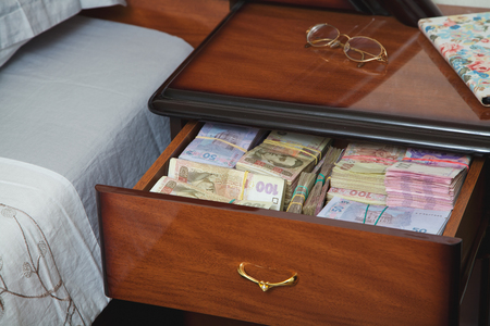 hidden costs: Bundles of banknotes in bedside table filled with Ukrainian cash
