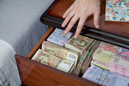 bedside table: Hand reaches for the money in bedside table filled with Ukrainian cash