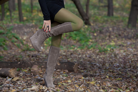 knees bent: Girl in green stockings in autumn forest gracefully bent leg in suede boots Stock Photo