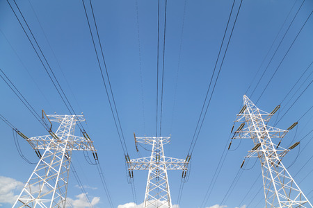 electrical equipment: Power transmission high voltage lines on the white supports against blue sky