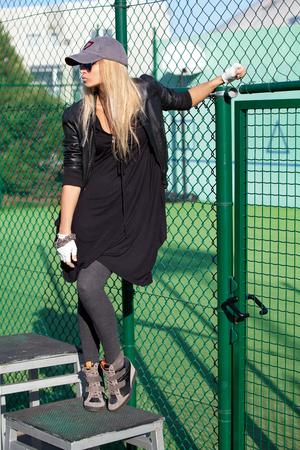 baseball caps: Glamorous blonde with long hair posing near slatted fence