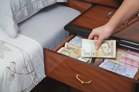 stingy: Hand pulls out wad of money from the bedside table filled with Ukrainian cash Stock Photo