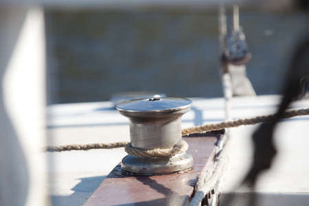 Rope stretched around a winch on a sailing vessel closeup