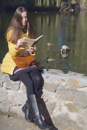 parapet: Beautiful thoughtful girl-student sits on parapet near the city pond in sunny autumn day